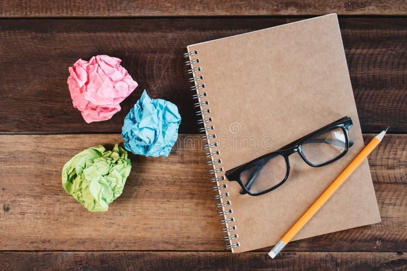 Carta sgualcita variopinta, occhiali, matita e un blocco note a spirale su una tavola di legno fotografia stock