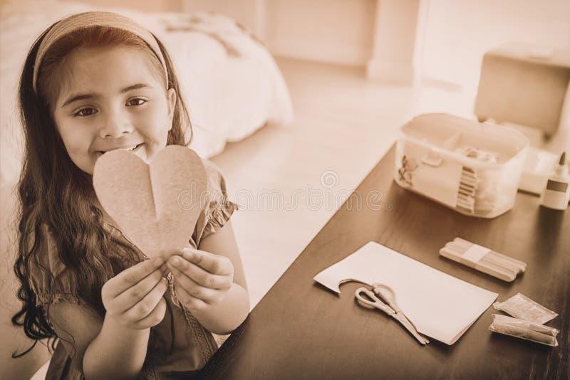 Carta sveglia del heartshape della tenuta della ragazza alla tavola illustrazione di stock