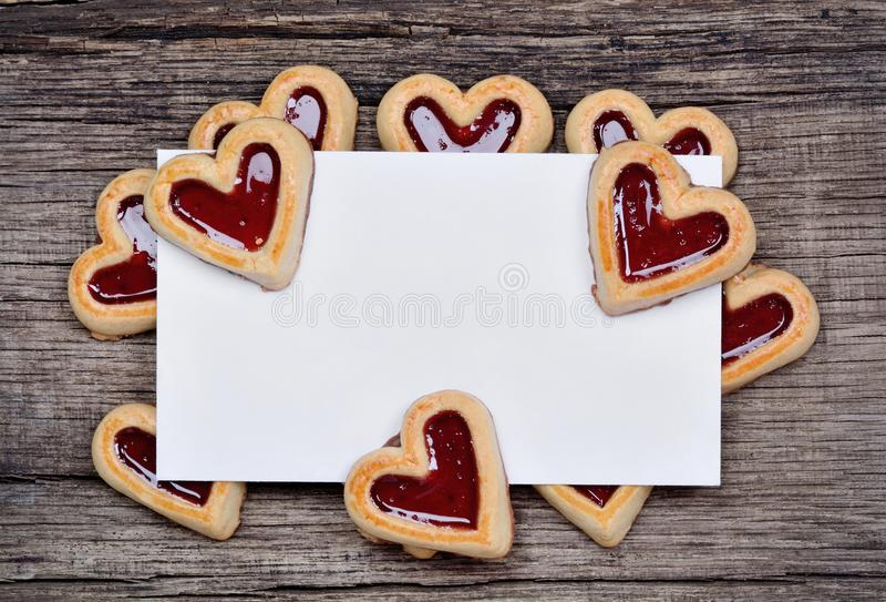 Carta vuota con molti biscotti del cuore sulla tavola rustica immagine stock