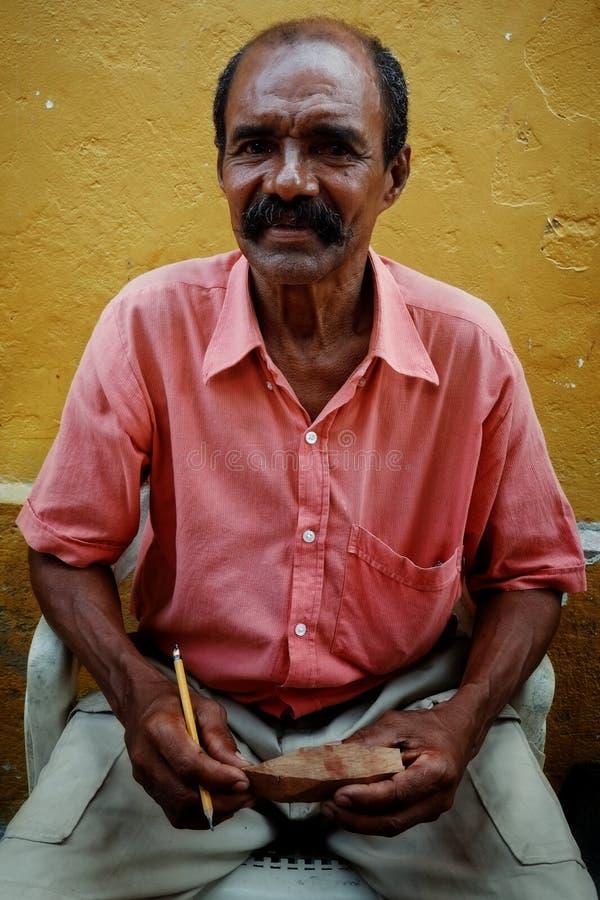 Cartagena/Colômbia - 19 DE MARÇO DE 2016: artista da rua que cinzela um veleiro pequeno para a venda na cidade velha na frente de fotografia de stock royalty free