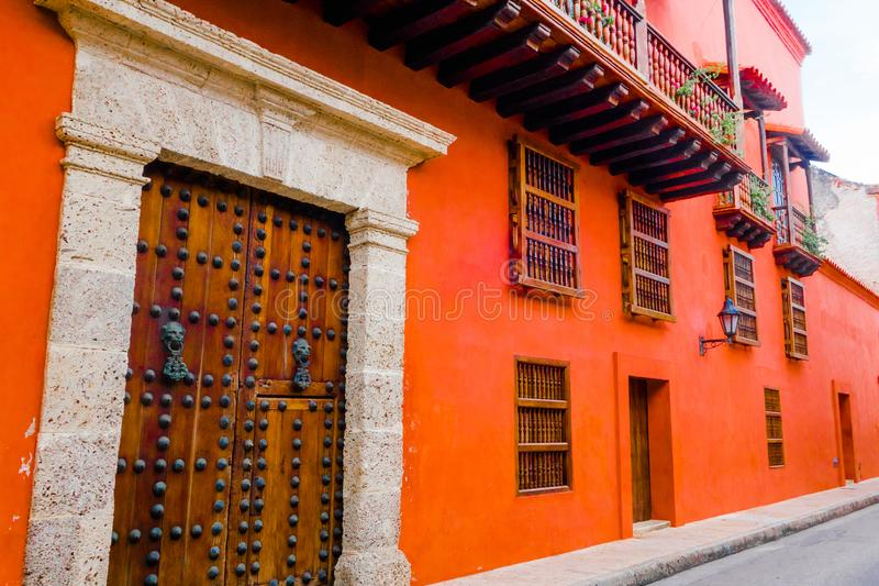 CARTAGENA, COLOMBIA 22, 2017: Cartagena city street with orange building and gorgeous wooden huge door of Cartagena. Walled City royalty free stock image