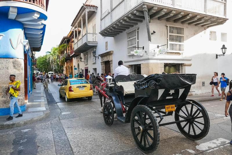 CARTAGENA, COLOMBIA - 5 de agosto de 2019: escena de la calle de un coche tirado por un caballo a través de una calle muy transit fotos de archivo libres de regalías