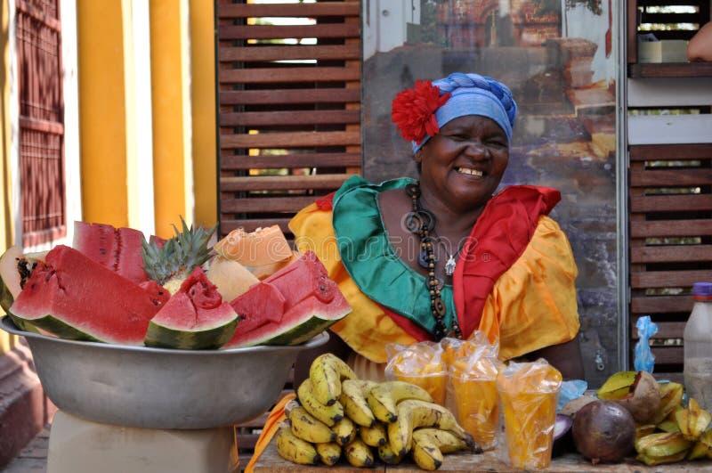 CARTAGENA COLOMBIA - JULI 30: Den Palenquera kvinnan säljer frukt på Juli 30, 2016 i Cartagena, Colombia Palenqueras är ett unikt arkivbilder