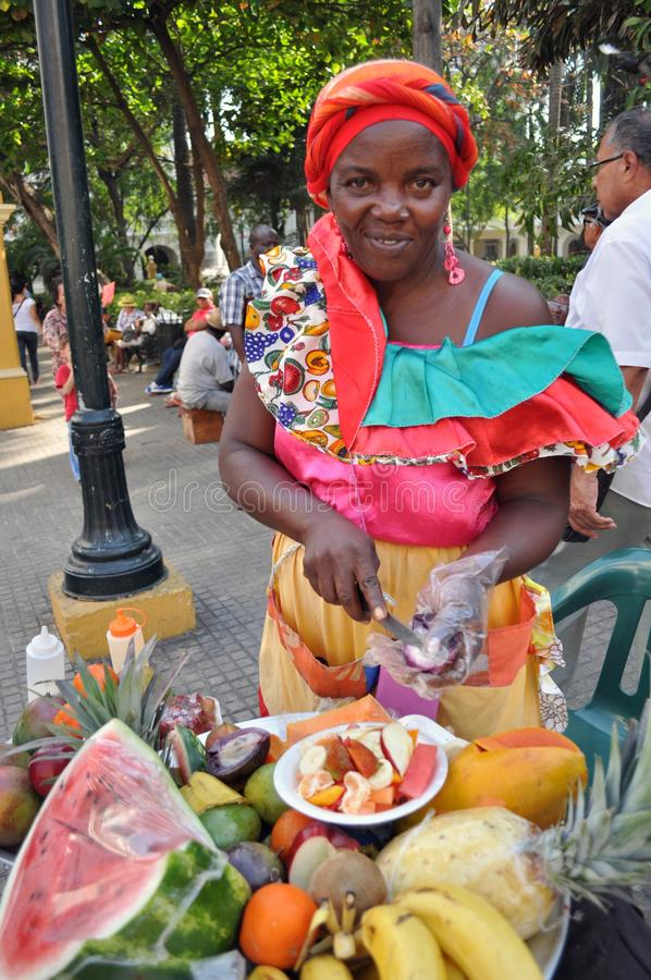 CARTAGENA, COLOMBIA - JULY 30: Palenquera woman sells fruit on July 30, 2016 in Cartagena, Colombia. Palenqueras are a unique. African descendant ethnic group stock photography