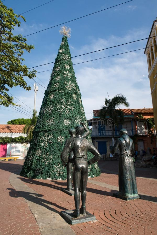 Cartagena de Indias, Bolivar/Colombia, 10 décembre 2017 : Quelques statues donnant sur un arbre de Noël décoré sur une place en photo libre de droits