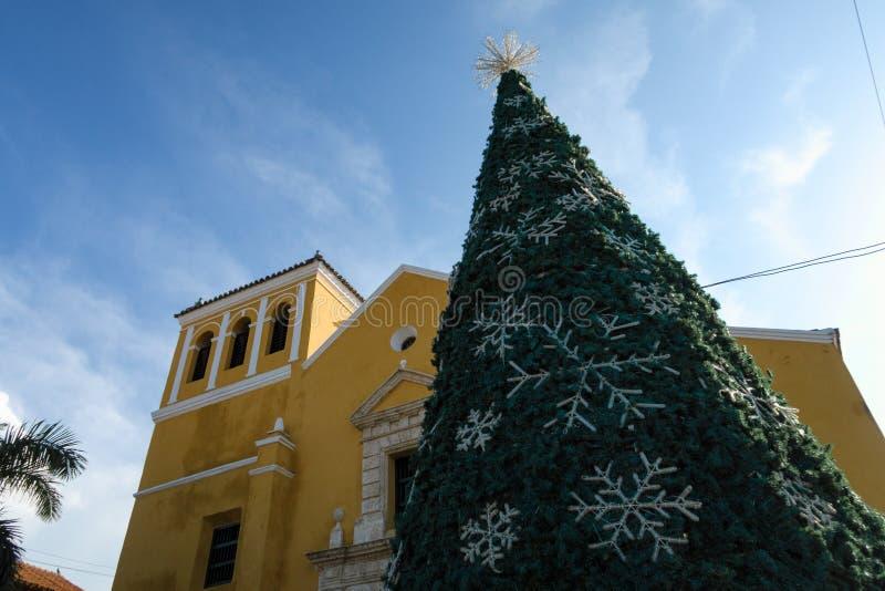 Cartagena de Indias, Bolivar/Colombia, 10 décembre 2017 : Un arbre de Noël décoré et devant une église jaune à Carthagène photos stock