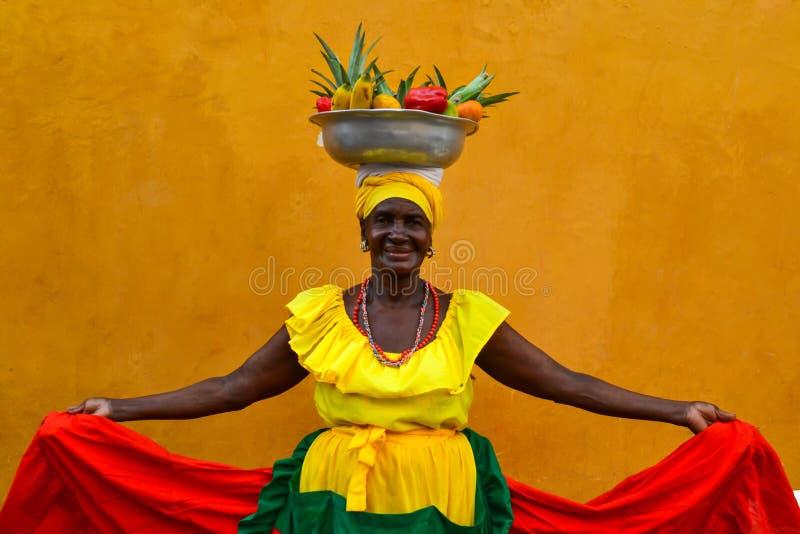 CARTAGENA DE INDIAS, COLOMBIA - Juli 27, 2017: Den härliga le kvinnan som bär traditionell dräktförsäljning, bär frukt i mitten a arkivfoton