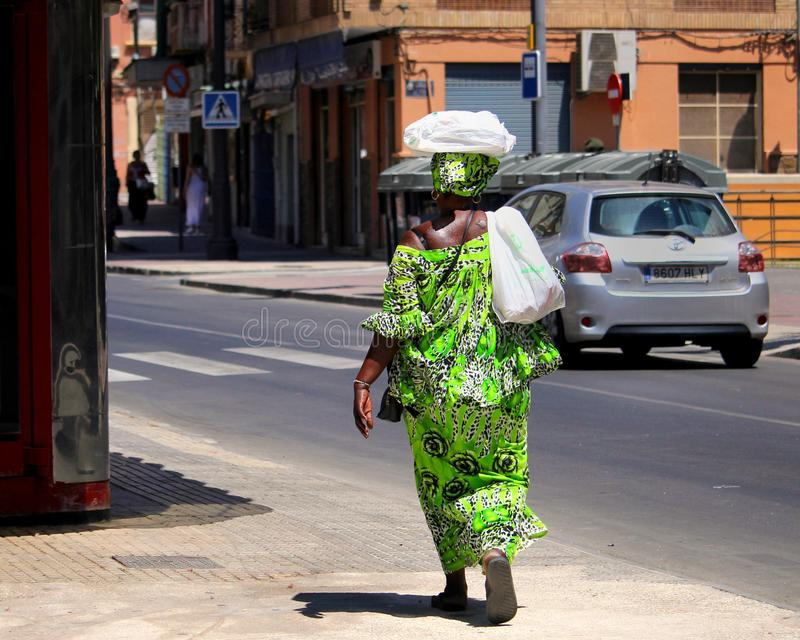 Cartagena, Murcia, Spain - August 01 2018: An Afro-Caribbean woman in bright green traditional african clothing, carrying goods on. Her head through a sunny royalty free stock image