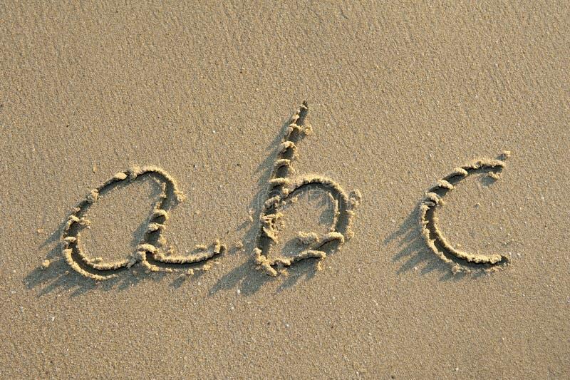 Cartas del alfabeto en arena en la playa fotos de archivo libres de regalías