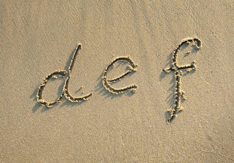 Cartas del alfabeto en arena en la playa imagenes de archivo