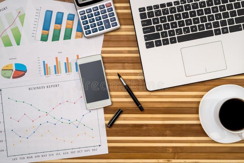 Cartas y gráficos de negocio con el ordenador portátil, taza de café fotos de archivo