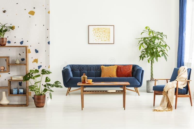 Cartaz acima do canapé azul no interior branco do apartamento com poltrona, a tabela de madeira e as plantas Foto real fotos de stock
