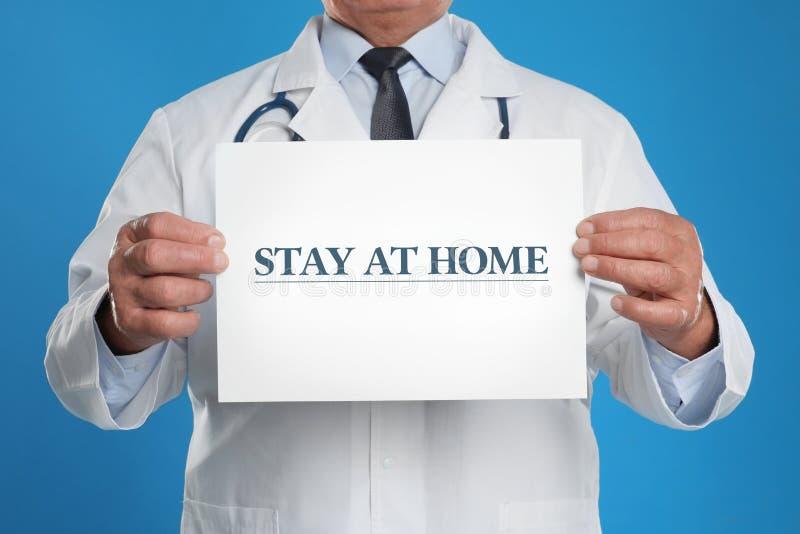 Cartaz com o texto STAY AT HOME em segundo plano, fechar Quarentena durante o surto de coronavírus fotos de stock royalty free