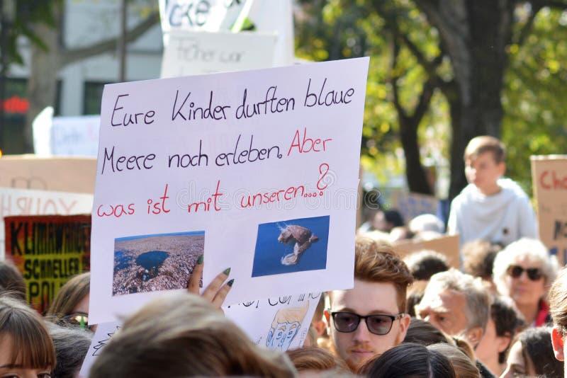 Cartaz de protesto dizendo 'Seus filhos ainda têm que ver oceanos azuis' retidos por jovens durante a Greve Climática Global fotos de stock royalty free