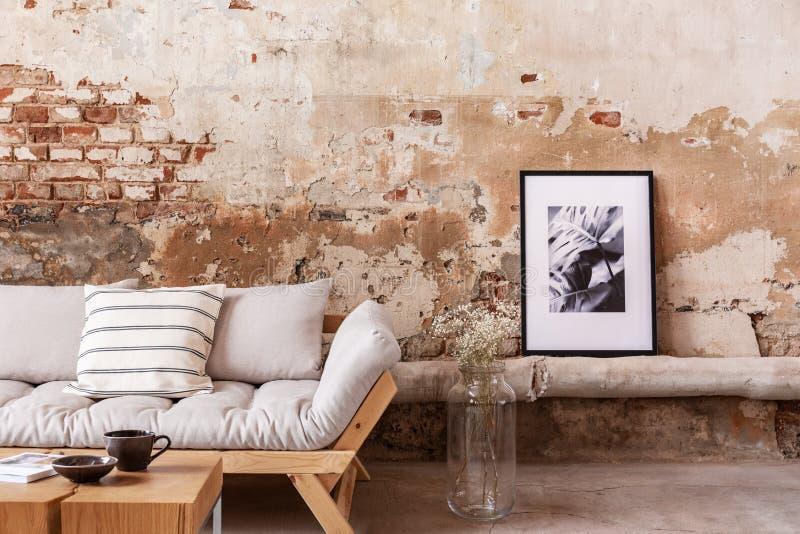 Cartaz e flores ao lado do sofá de madeira cinzento com os descansos em horizontalmente interior com parede de tijolo fotos de stock