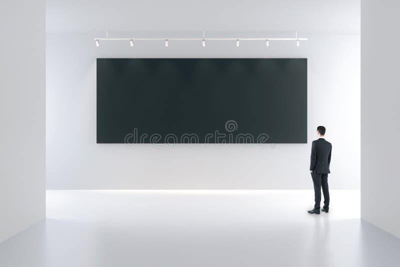 Cartaz e homem de negócios pretos vazios na sala vazia branca fotos de stock