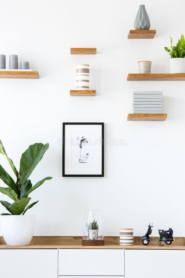 Cartaz na parede branca acima do armário de madeira com a planta em simples imagem de stock