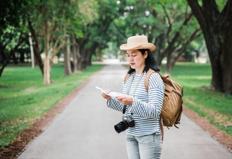Carte asiatique d'utilisation de voyageur de sac ? dos de femme en voyageant au concept forestHoliday de vacances de pluie Mode d photographie stock libre de droits