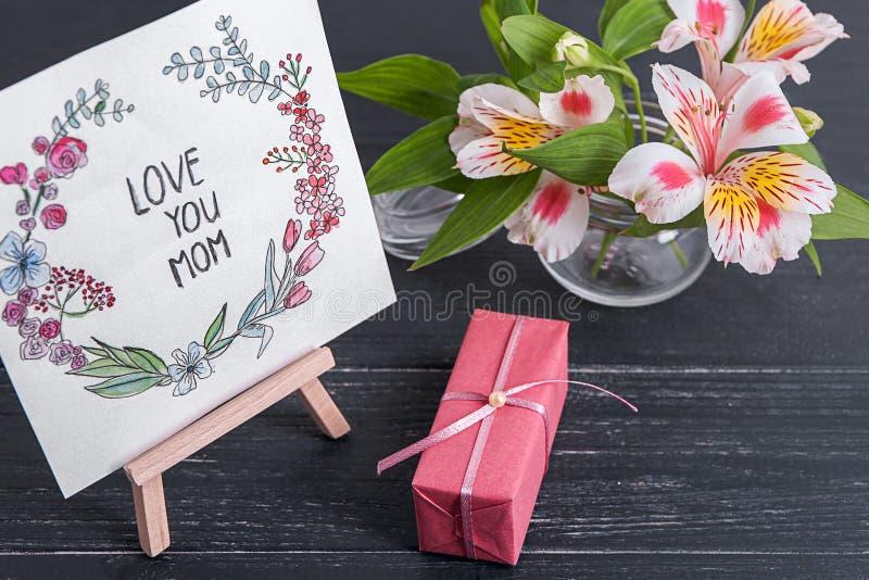 Carte avec amour d'expression vous maman, fleurs et boîte-cadeau sur la table Salutation pour le jour de m?re photo libre de droits