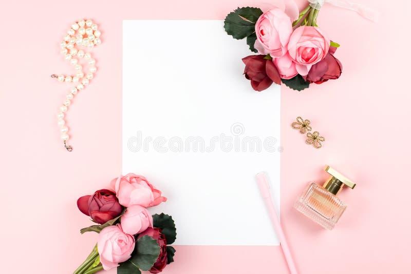 Carte avec le cadre de stylo, de bijoux, de parfum, rouge et rose de fleurs sur le fond en pastel Salutation pour le jour des fem image stock