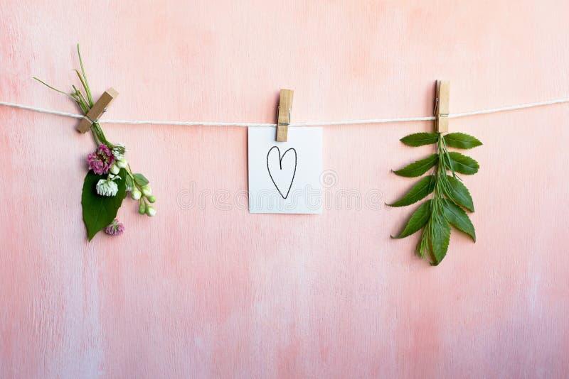 Carte avec le coeur peint à la main accroché sur la corde Fond floral rose-clair photos stock
