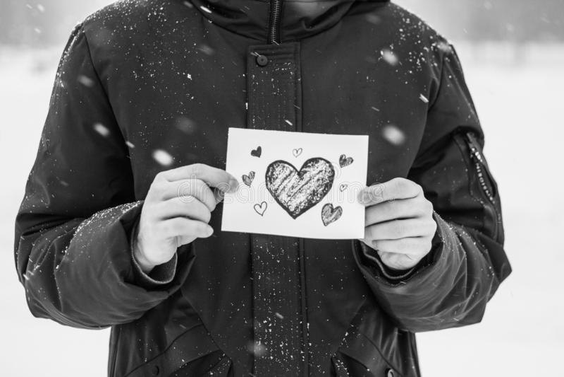 carte avec un coeur rouge dans les mains d'un homme, déclaration de l'amour photo stock