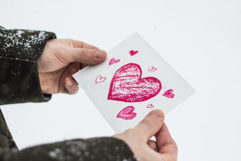 carte avec un coeur rouge dans les mains d'un homme, déclaration de l'amour photographie stock libre de droits