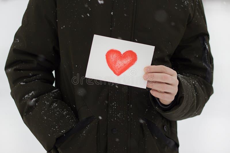 carte avec un coeur rouge dans les mains d'un homme, déclaration de l'amour photos libres de droits