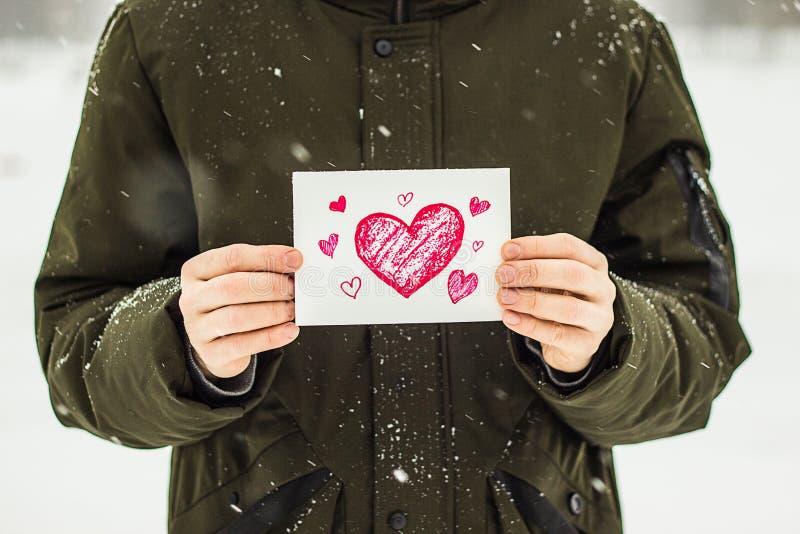 carte avec un coeur rouge dans les mains d'un homme, déclaration de l'amour photo libre de droits