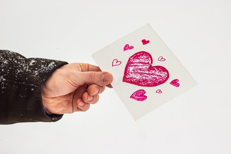 carte avec un coeur rouge dans les mains d'un homme, déclaration de l'amour photos stock