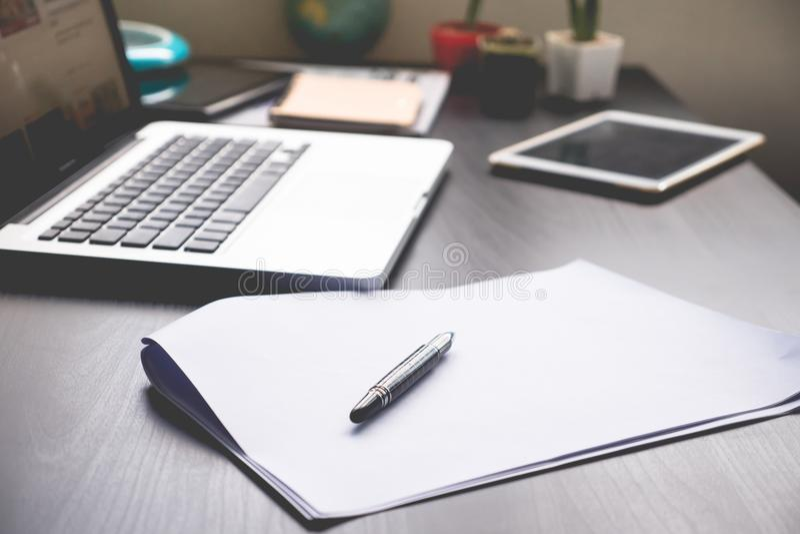 Carte in bianco con la penna, la compressa ed il computer portatile sullo scrittorio fotografie stock