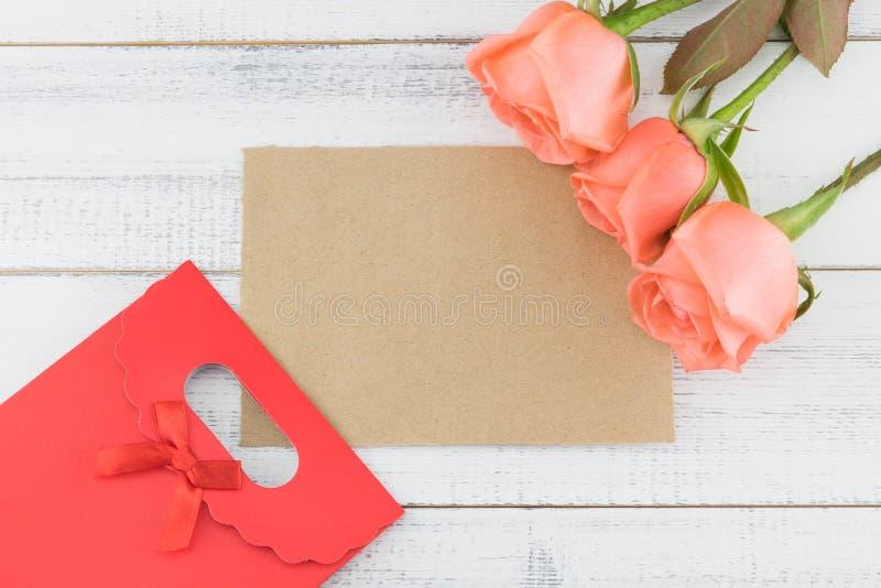 Carte brune vierge et sac rouge de cadeau décorés des roses oranges images stock