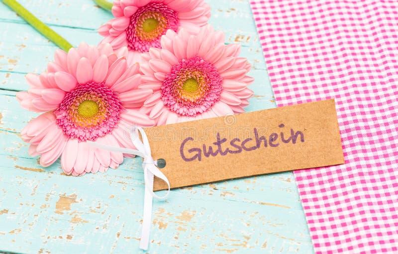 Carte cadeaux con palabra alemana, Gutschein, vale de los medios o cupón y flores rosadas hermosas imagen de archivo libre de regalías
