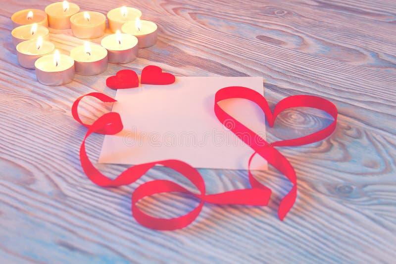 Carte cadeaux pour le jour du ` s de Valentine avec les bougies et le ruban rouge de satin sur le fond en bois bleu image libre de droits