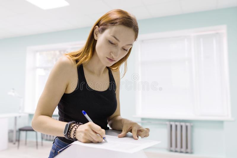 Carte d'ufficio di firma della giovane bella donna all'interno fotografia stock libera da diritti