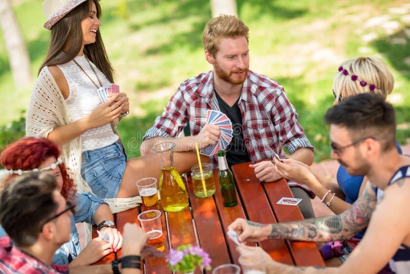 Carte da gioco all'aperto con le bevande e gli amici fotografia stock libera da diritti