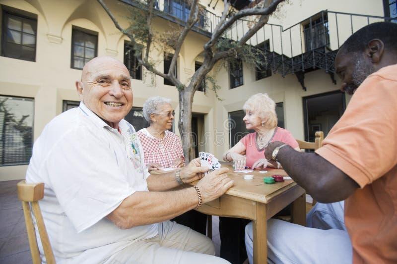 Carte da gioco dell'uomo senior con gli amici fotografie stock