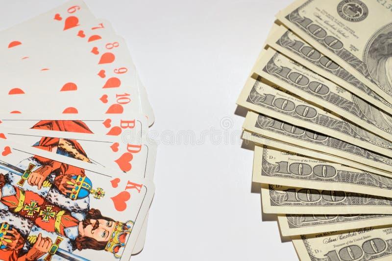 Carte da gioco nelle banconote di un dollaro di fila in un fan immagini stock