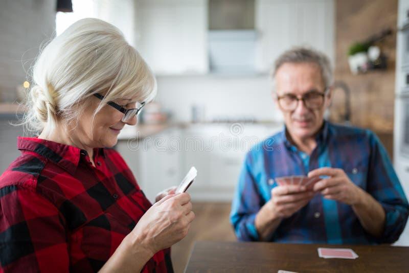 Carte da gioco senior felici della donna con il suo marito immagini stock libere da diritti