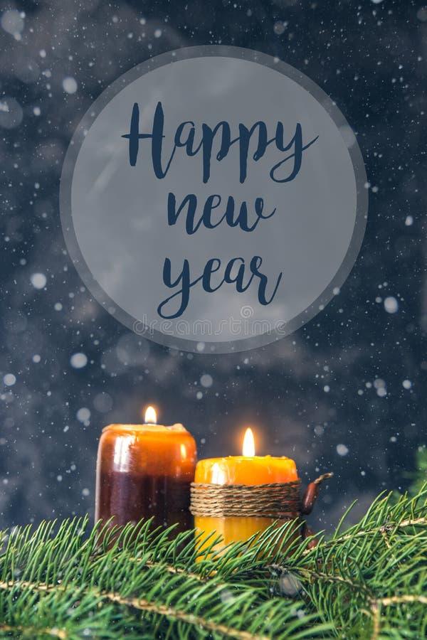 Carte de bonne année avec des bougies, des branches de sapin et la neige images stock