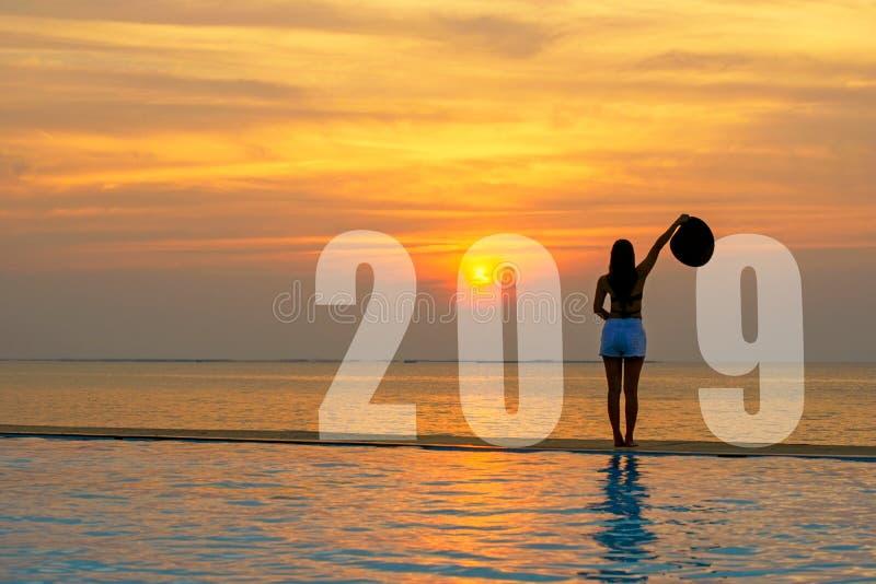 Carte 2019 de bonne année de femme de mode de vie Détente et liberté de femme de silhouette sur la piscine près de la mer et la p photo libre de droits