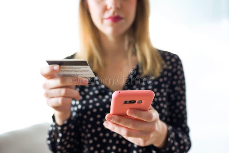 Carte de crédit blanche de participation sérieuse de jeune femme pour faire des emplettes en ligne avec le téléphone portable dan photos libres de droits