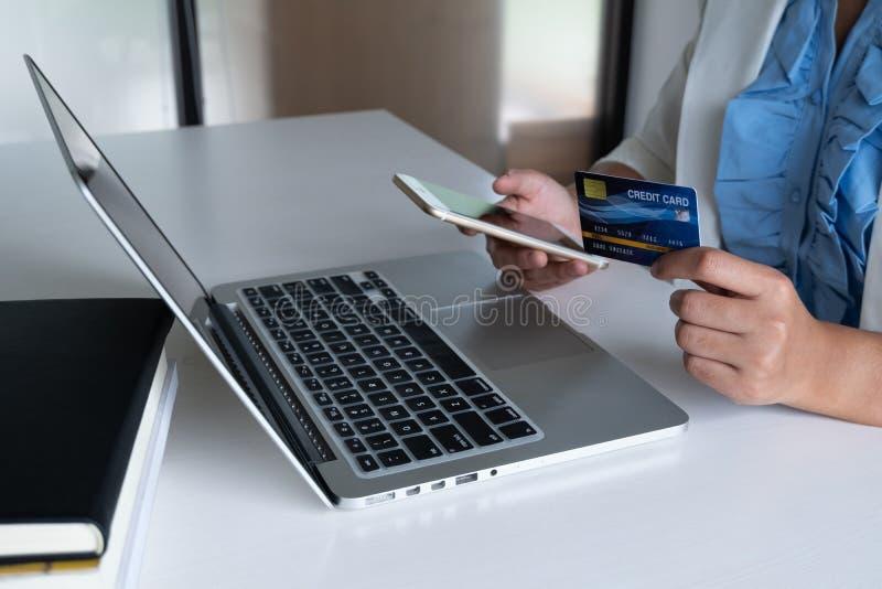 Carte de crédit d'utilisation de femme pour des achats en ligne à son ordinateur portable et téléphone image stock