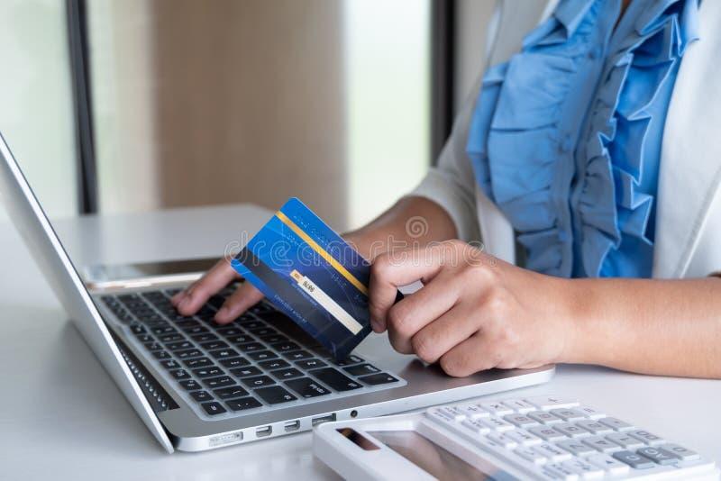 Carte de crédit d'utilisation de femme pour des achats en ligne à son ordinateur portable et téléphone photo stock