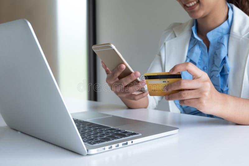 Carte de crédit d'utilisation de femme pour des achats en ligne à son ordinateur portable et téléphone image libre de droits