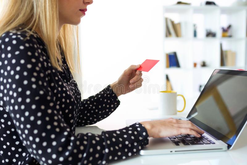 Carte de crédit rouge de participation sûre de jeune femme pour faire des emplettes en ligne avec l'ordinateur à la maison photos libres de droits