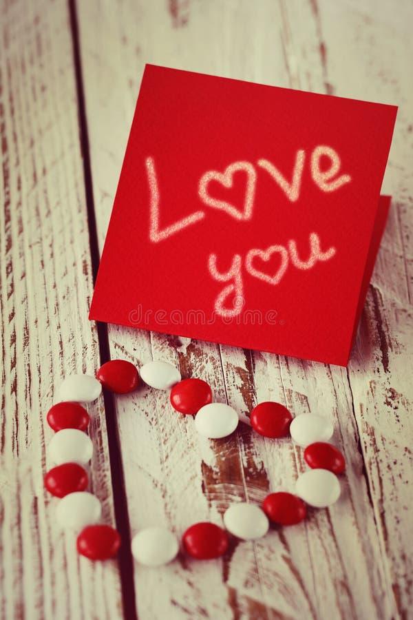 Carte de jour du ` s de Valentine avec de petits coeurs et sucrerie blanche rouge tonalité de l'image image libre de droits