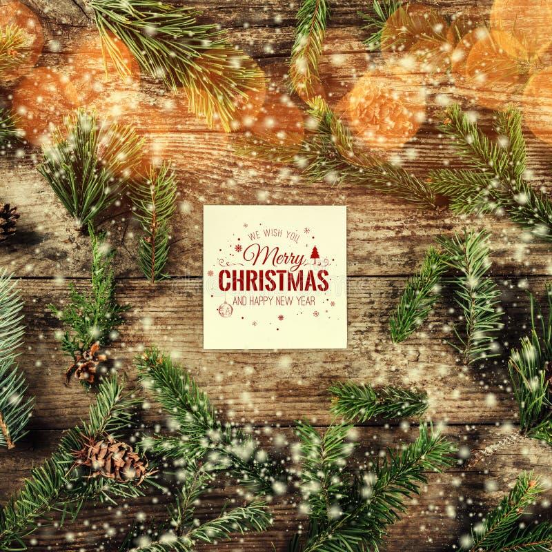 Carte de Joyeux Noël et de nouvelle année sur le fond en bois avec des branches de sapin, des cônes de pin et des flocons de neig illustration libre de droits