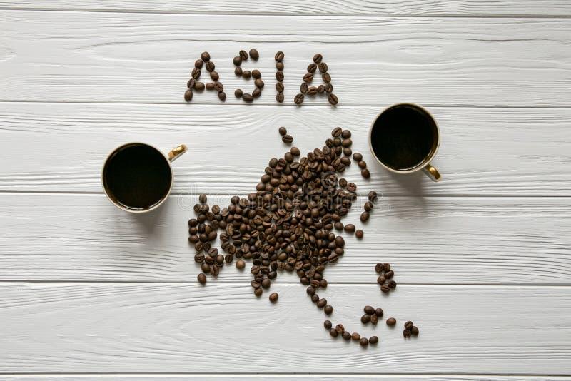 Carte de l'Asie faite de grains de café rôtis s'étendant sur le fond texturisé en bois blanc avec deux tasses de café image libre de droits