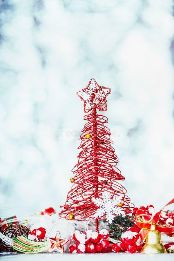 Carte de Noël avec l'arbre rouge, l'étoile et la décoration de fête sur le fond bleu de bokeh d'hiver photo stock